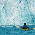 A student paddles by a glacier in the Alaskan rain forest.