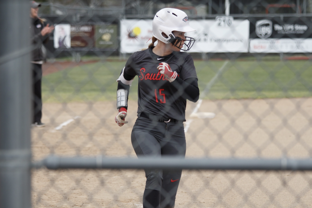Softball player Olivia Mackey runs in with batter helmet on