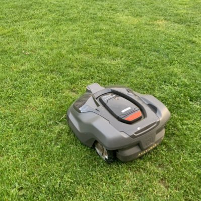 SOU's new, automated mower resembles a small Roomba vacuum sitting on grass.